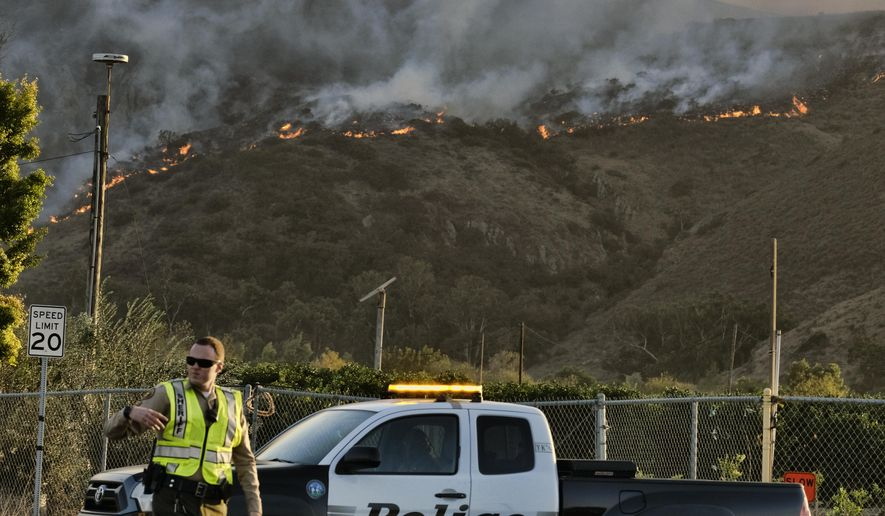 A police officer directs traffic at a checkpoint in front of an advancing wildfire Thursday, Nov. 8, 2018, near Newbury Park, Calif. The Ventura County Fire Department has also ordered evacuation of some communities in the path of the fire, which erupted a few miles from the site of Wednesday night's deadly mass shooting at a Thousand Oaks bar. (AP Photo/Richard Vogel)