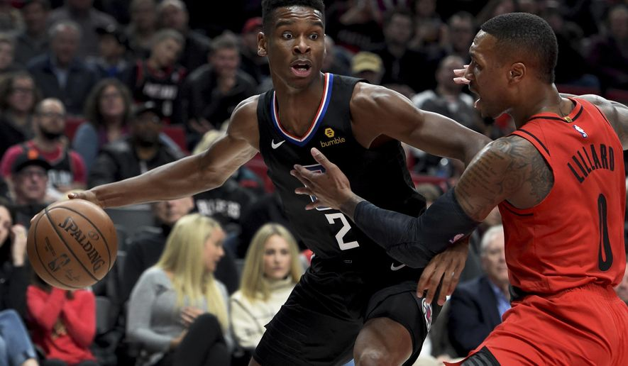 Los Angeles Clippers guard Shai Gilgeous-Alexander, left, tries to get past Portland Trail ...