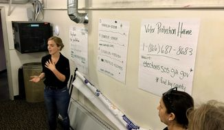 Helen Brosnan, of the National Domestic Workers Alliance, trains volunteers who are working the phones in a warehouse, Friday, Nov. 9, 2018, in Atlanta, where they are frantically trying to reach Georgians who voted with provisional ballots to make sure their votes are counted. (AP Photo/Jeff Martin)