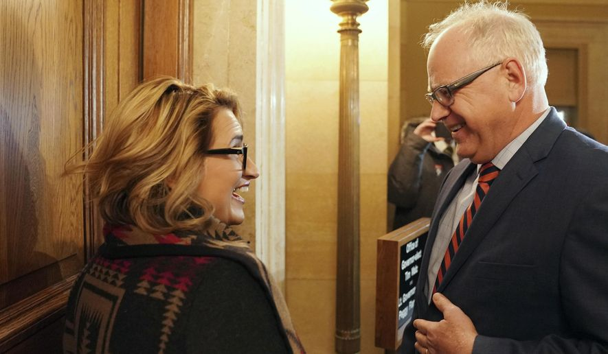 Lt. Gov.-elect Peggy Flanagan and Gov.-elect Tim Walz talk to each other before opening the door to their transition offices at the state Capitol Thursday, Nov. 8, 2018, in St. Paul, Minn. (Anthony Souffle/Star Tribune via AP)