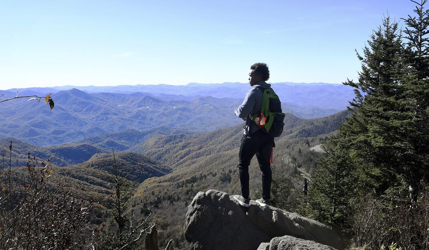 In this Oct. 30, 2018 photo, Joshua Perkins takes in the view from the top of Waterrock Knob on the Blue Ridge Parkway in Maggie Valley, N.C., as he hikes with Pathways to Parks. Pathways to Parks is an outdoors group that aims to get more people of color outside and enjoying National Parks. (Angeli Wright/The Asheville Citizen-Times via AP)