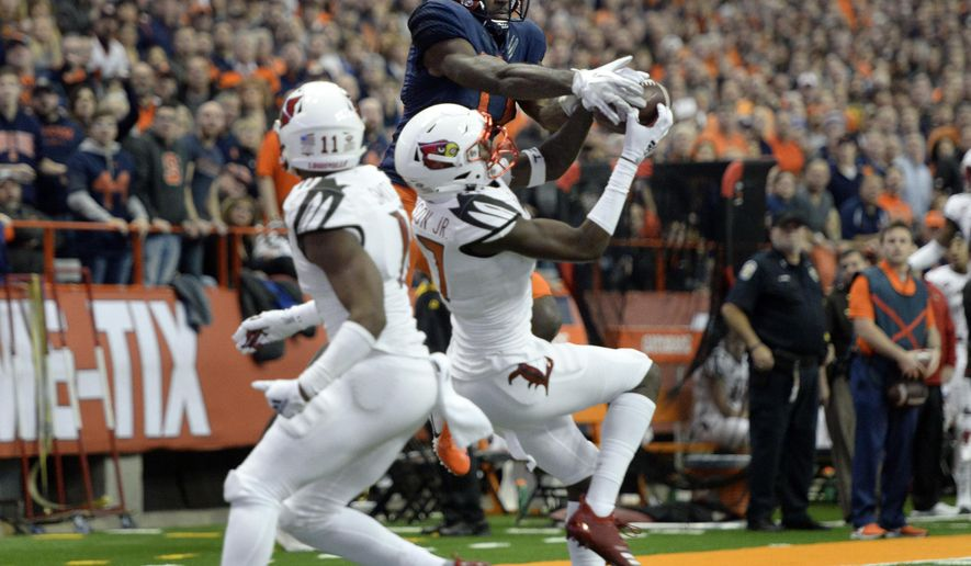 Louisville cornerback Anthony Johnson, center, breaks up a pass intended for Syracuse wide receiver Jamal Custis during the first half of an NCAA college football game in Syracuse, N.Y., Friday, Nov. 9, 2018. (AP Photo/Adrian Kraus)