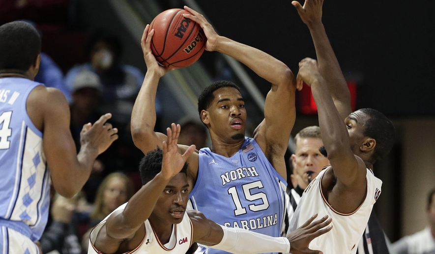 North Carolina's Garrison Brooks (15) looks to pass while Elon's Kris Wooten, left, and Chuck Hannah guard during the first half of an NCAA college basketball game in Elon, N.C., Friday, Nov. 9, 2018. (AP Photo/Gerry Broome)