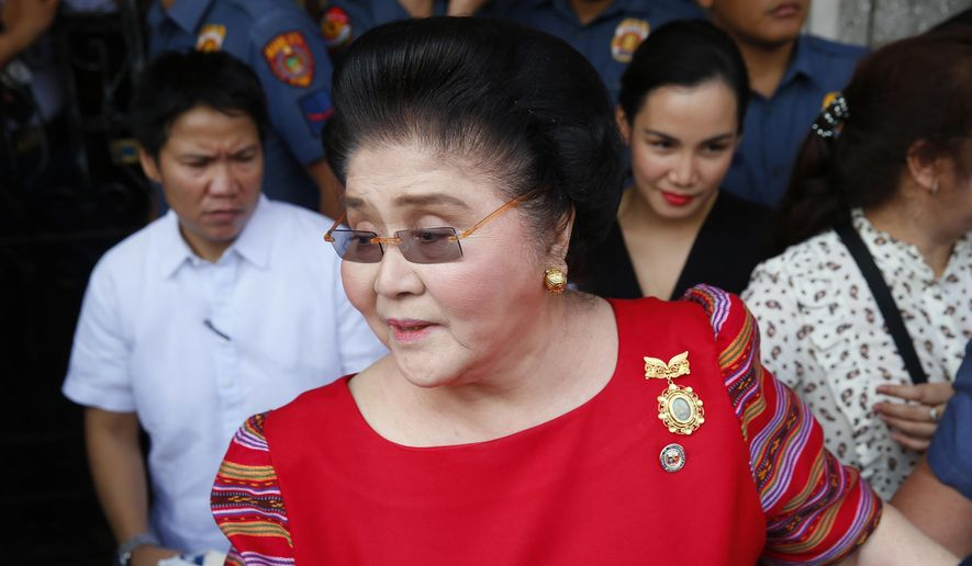 FILE - In this Oct. 16, 2018, file photo, former Philippines first lady and widow of the late dictator Ferdinand Marcos, Congresswoman Imelda Marcos arrives at the Commission on Elections to lend her support for her daughter Governor Imee Marcos in filing her Certificate of Candidacy or COC for a Senate seat in the May 2019 midterm elections in Manila, Philippines. A Philippine court found former first lady Imelda Marcos guilty of graft and ordered her arrest Friday, Nov. 9, 2018, in a rare conviction among many corruption cases that she's likely to appeal to avoid jail and losing her seat in Congress. (AP Photo/Bullit Marquez, File)