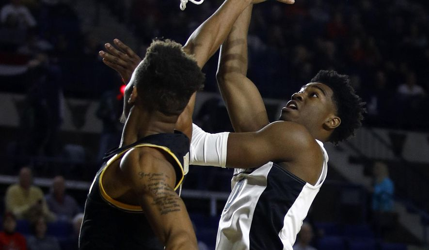 Providence guard A.J. Reeves, right, shoots over Wichita State guard Dexter Dennis in the first half of an NCAA college basketball game at the Veterans Classic tournament in Annapolis, Md., Friday, Nov. 9, 2018. (AP Photo/Patrick Semansky)