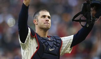 FILE - In this Sunday, Sept. 30, 2018, file photo, Minnesota Twins' Joe Mauer acknowledges a standing ovation as he donned catcher's gear and caught for one pitch against a Chicago White Sox batter in the ninth inning of a baseball game  in Minneapolis. Mauer began his career as a catcher before switching to first base. The Minneapolis Star Tribune reports that Mauer has taken out an ad in its Sunday, Nov. 11, 2018, paper to announce his retirement. (AP Photo/Jim Mone, File)
