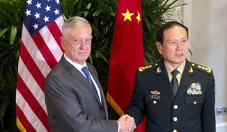 In this Thursday, Oct. 18, 2018, file photo, U.S. Defense Secretary Jim Mattis, left, meets Chinese Defense Minister Wei Fenghe in Singapore. (AP Photo/Robert Burns, File)