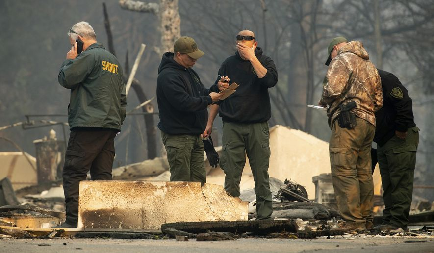 Sheriff's deputies recover the remains of Camp Fire victims on Saturday, Nov. 10, 2018, in Paradise, Calif.. (AP Photo/Noah Berger)