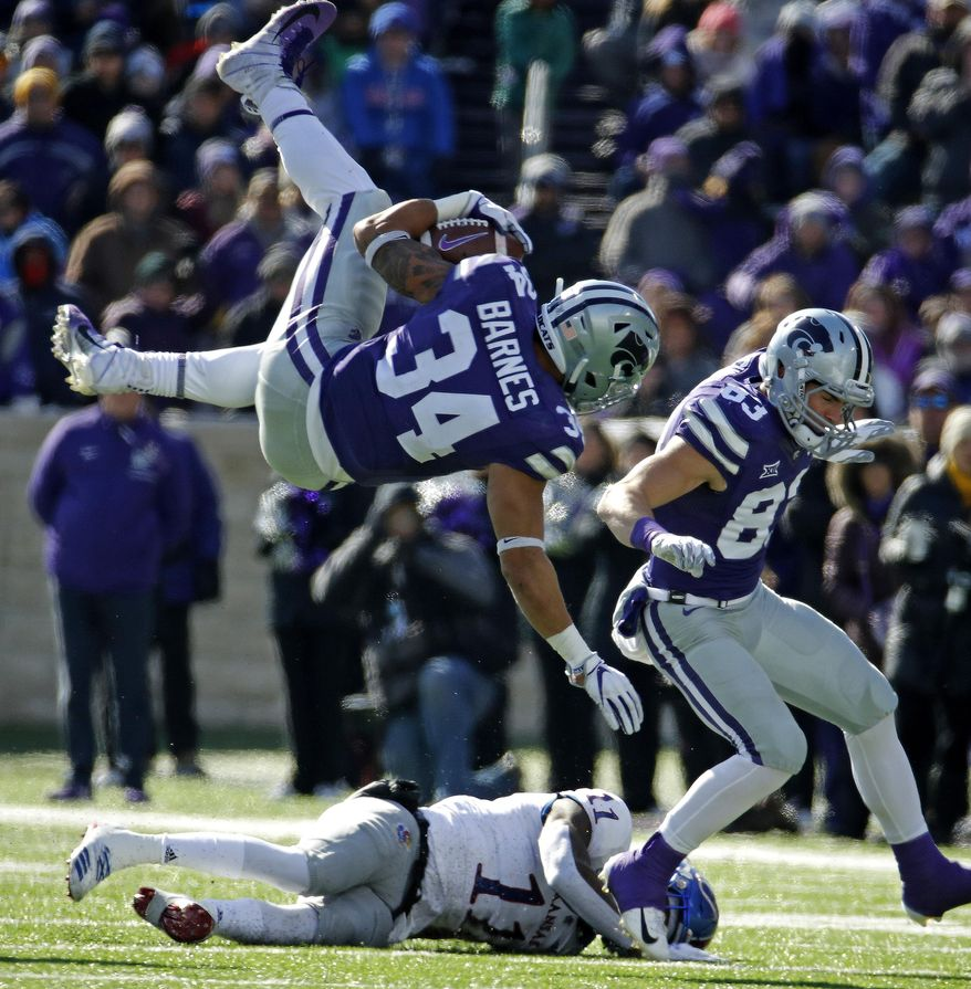 Kansas State running back Alex Barnes (34) leaps over Kansas safety Mike Lee (11) as he runs for a first down during the first half of an NCAA college football game Saturday, Nov. 10, 2018, in Manhattan, Kan. (AP Photo/Charlie Riedel)