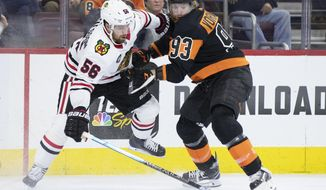 Chicago Blackhawks' Erik Gustafsson, left, of Sweden, and Philadelphia Flyers' Jakub Voracek, right, of the Czech Republic, battle for the puck during the second period of an NHL hockey game, Saturday, Nov. 10, 2018, in Philadelphia. (AP Photo/Chris Szagola)