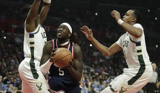Los Angeles Clippers' Montrezl Harrell, center, looks to shoot under pressure by Milwaukee Bucks' Tony Snell, left, and John Henson during the first half of an NBA basketball game Saturday, Nov. 10, 2018, in Los Angeles. (AP Photo/Jae C. Hong)