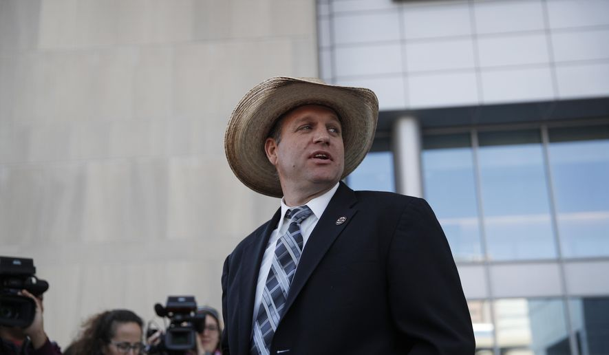 In this Dec. 20, 2017 file photo, Ammon Bundy walks out of a federal courthouse in Las Vegas.  (AP Photo/John Locher, File) **FILE**