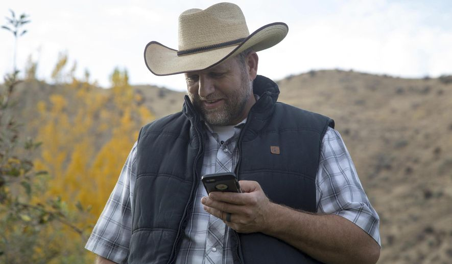 """In this undated photo, Ammon Bundy receives a call from a former fellow inmate while picking Gypsy Lust apples in his orchard in Emmett, Idaho. Bundy calls himself a """"sunlight kind of guy."""" Before his family's infamous standoffs near Bunkerville, Nevada, and Burns, Oregon, he was living in the dark, he told the Idaho Statesman. Now he's got a new view on life that he's eager to share, he said, and some Idahoans are eager to listen. (Kelsey Grey/Idaho Statesman via AP)"""