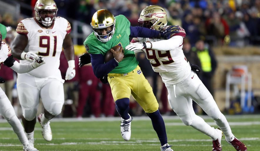 Notre Dame quarterback Brandon Wimbush, center, tries to break the tackle of Florida State defensive end Brian Burns, right, as Florida State defensive lineman Robert Cooper (91) watches in the first half of an NCAA college football game in South Bend, Ind.,Saturday, Nov. 10, 2018. (AP Photo/Paul Sancya)