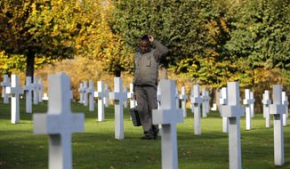 A cemetery employee walks between graves of American serviceman killed during WWI ahead of celebrations of the WWI centenary at the American Cemetery in Suresnes, on the outskirts of Paris, France, Friday, Nov. 9, 2018. World War I ended on Nov. 11, 1918. (AP Photo/Vadim Ghirda)