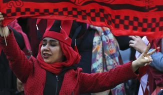 A female Iranian spectator waves a flag of her favorite team Persepolis prior to start their soccer match with Japan's Kashima Antlers during the 2nd leg of the Asian Champions League finals at the Azadi (freedom) stadium in Tehran, Iran, Saturday, Nov. 10, 2018. Authorities allowed a select group of women into Azadi stadium to watch men's soccer match, a rare move in the Islamic theocracy. Since the 1979 Islamic Revolution women have not been allowed to watch men's soccer matches in stadiums, though they have occasionally been allowed to watch volleyball and basketball in stadiums. (AP Photo/Vahid Salemi)