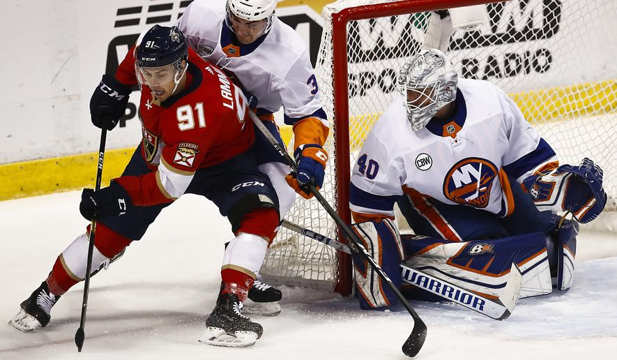 Florida Panthers right wing Juho Lammikko, left, and New York Islanders defenseman Adam Pelech, right, both go for the puck during the first period of an NHL hockey game on Saturday, Nov. 10, 2018, in Sunrise, Fla. (AP Photo/Brynn Anderson)