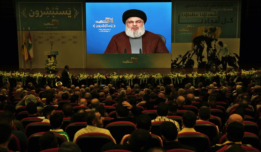Supporter of the Iranian-backed Hezbollah group listen to a speech of Hezbollah leader Sayyed Hassan Nasrallah, via a video link, during a rally marking Hezbollah Martyr's Day, in a southern suburb of Beirut, Lebanon, Saturday, Nov. 10, 2018. (AP Photo/Bilal Hussein)