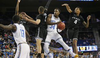 UCLA guard David Singleton, second from right, weaves through defense of Long Beach State's Deishuan Booker, Ron Freeman, and KJ Byers, from left, while UCLA guard Kris Wilkes, front left, watches during the first half of an NCAA college basketball game Friday, Nov. 9, 2018, in Los Angeles. (AP Photo/Danny Moloshok)