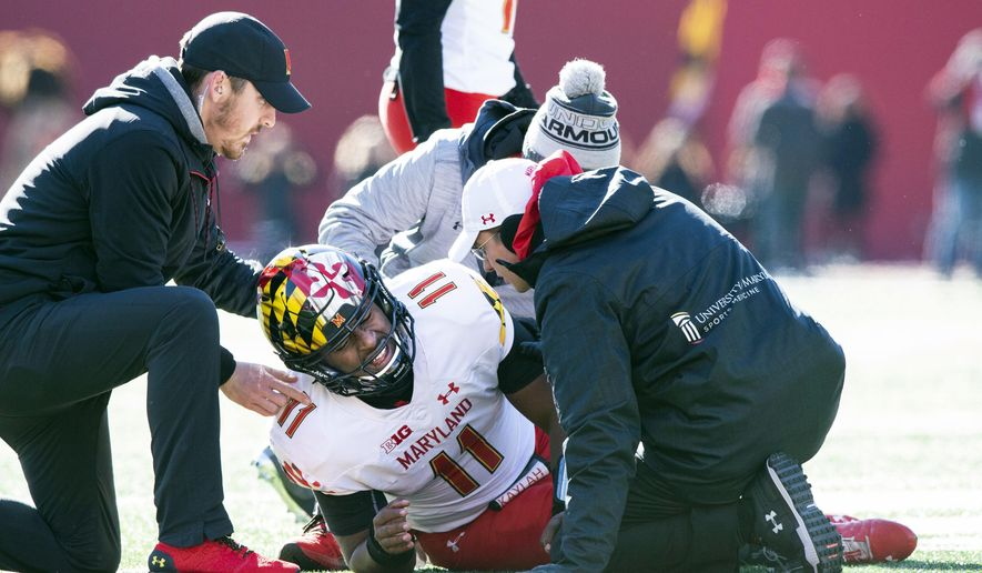 Maryland quarterback Kasim Hill (11) grimaces as he is examined by team trainers after an apparent injury during the first half of an NCAA college football game against Indiana, Saturday, Nov. 10, 2018, in Bloomington, Ind. (AP Photo/Doug McSchooler) ** FILE **