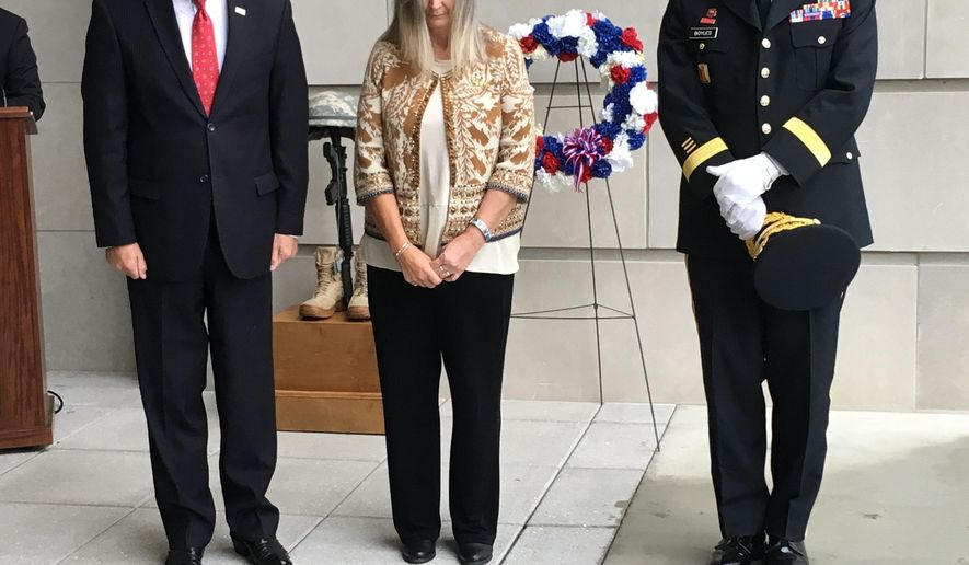 """In this Nov. 9, 2018, photo, Mississippi Gov. Phil Bryant, left, prays with Donna Bagwell, in Jackson, Miss., whose son was killed in 2005 in Iraq while serving in the U.S. Marine Corps, and Maj. Gen. Janson """"Durr"""" Boyles, adjutant general of the Mississippi National Guard. They took part in a wreath-laying ceremony to honor military veterans outside the Museum of Mississippi History and the Mississippi Civil Rights Museum. (AP Photo/Emily Wagster Pettus)"""