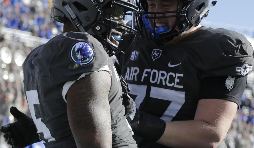 Air Force quarterback Donald Hammond III (5) celebrates a touchdown run with teammate Taven Birdow (33) during the first half of an NCAA college football game against New Mexico, Saturday, Nov. 10, 2018, at Air Force Academy, Colo. (AP Photo/Jack Dempsey)