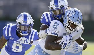 North Carolina's Michael Carter (8) runs the ball while Duke's Jeremy McDuffie (9) and Marquis Waters move in for the tackle during the first half of an NCAA college football game in Durham, N.C., Saturday, Nov. 10, 2018. (AP Photo/Gerry Broome)