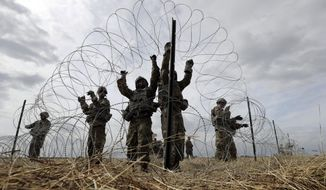 Members of a U.S Army engineering brigade place concertina wire around an encampment for troops, and personnel from the Department of Defense and U.S. Customs and Border Protection near the U.S.-Mexico International bridge, Sunday, Nov. 4, 2018, in Donna, Texas. (AP Photo/Eric Gay) **FILE**