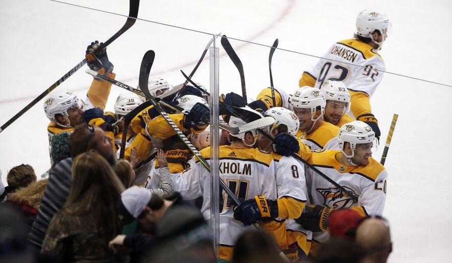 Nashville Predators defenseman Mattias Ekholm (14) is swarmed by teammates after his game-winning goal against the Dallas Stars during overtime of an NHL hockey game in Dallas, Saturday, Nov. 10, 2018. (AP Photo/Michael Ainsworth)