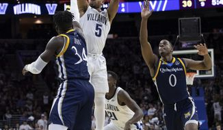Villanova's Phil Booth, center, shoots as Quinnipiac's Abdulai Bundu, left, and Aaron Robinson, right, defend during the first half of an NCAA college basketball game Saturday, Nov. 10, 2018, in Philadelphia. (AP Photo/Chris Szagola)