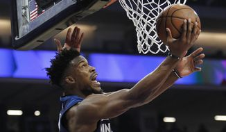 Minnesota Timberwolves guard Jimmy Butler (23) gets around Sacramento Kings guard Buddy Hield (24) for a basket during the first half of an NBA basketball game in Sacramento, Calif., Friday, Nov. 9, 2018. (AP Photo/Steve Yeater) **FILE**