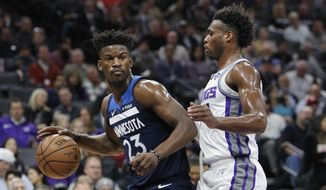 Minnesota Timberwolves guard Jimmy Butler (23) battles for position against Sacramento Kings guard Buddy Hield (24) during the first half of an NBA basketball game in Sacramento, Calif., Friday, Nov. 9, 2018. (AP Photo/Steve Yeater) **FILE**
