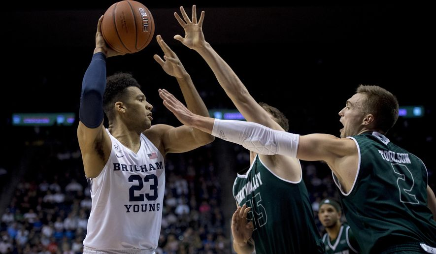 BYU forward Yoeli Childs (23) looks to pass the ball past Utah Valley center Richard Harward (55) and guard Jake Toolson (2) during an NCAA college basketball game Friday, Nov. 9, 2018, in Provo, Utah. (Isaac Hale/The Daily Herald via AP)