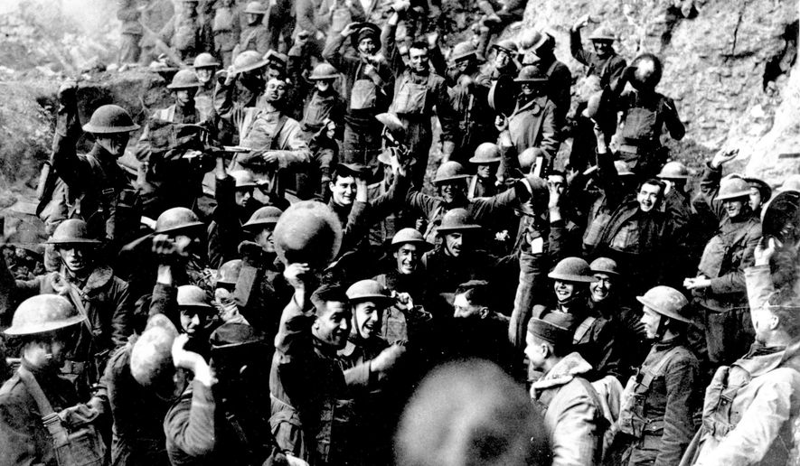 FILE In this Nov. 11, 1918 file photo, American troops cheer after hearing the news that the Armistice had been signed, ending World War I. At 11 a.m. on the 11th day of the 11th month of 2018, scores of world leaders are gathering in Paris to mark 100 years since the armistice that ended World War I entered into force, and to celebrate peace. (AP Photo, File)
