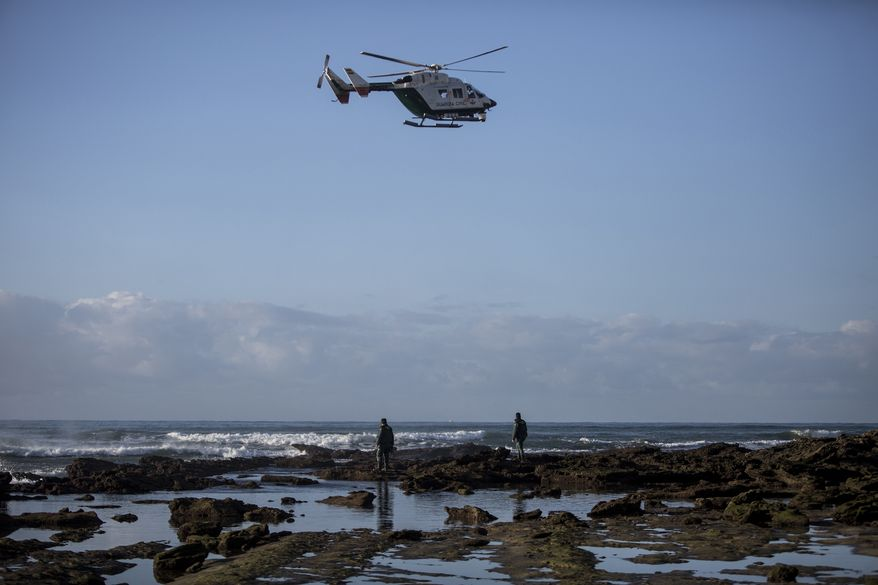 Members of Spanish Civil Guard with the help of a helicopter look for bodies of drowned migrants near the village of Canos de Meca in southern Spain, Tuesday, Nov. 6 2018. Spain's maritime rescue service says at least 17 people have died trying to reach Spanish territory in boats departing from North Africa but rescued 80 people Monday from two boats and recovered the bodies of 13 dead migrants in the Alboran Sea, part of the western Mediterranean route into Europe. In a separate incident, the Spanish Civil Guard says it found four bodies of migrants and 22 survivors, all men from northern Africa, after their wooden dinghy hit a reef. (AP Photo/Javier Fergo)