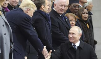 Russian President Vladimir Putin shakes hands with US President Donald Trump as he arrives to attend a ceremony at the Arc de Triomphe in Paris, Sunday, Nov. 11, 2018, as part of commemorations marking the 100th anniversary of the 11 November 1918 armistice, ending World War I. (Ludovic Marin/Pool Photo via AP)