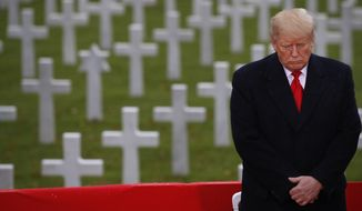 President Donald Trump stands in front of headstones during an American Commemoration Ceremony, Sunday Nov. 11, 2018, at Suresnes American Cemetery near Paris. Trump is attending centennial commemorations in Paris this weekend to mark the Armistice that ended World War I. (AP Photo/Jacquelyn Martin)