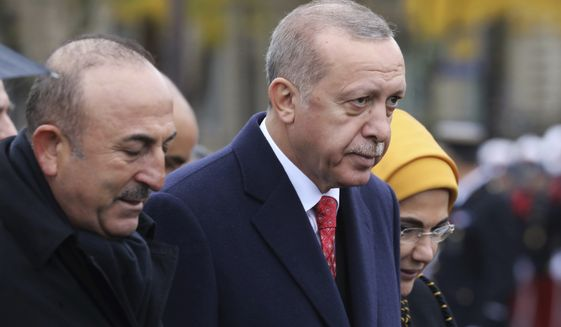 Turkish President Recep Tayyip Erdogan, right, and Turkish Foreign Minister Mevlut Cavusoglu leave the Arc de Triomphe after attending a ceremony as part of the commemorations marking the 100th anniversary of the 11 November 1918 armistice, ending World War I, Sunday, Nov. 11, 2018. (Ludovic Marin/Pool Photo via AP)