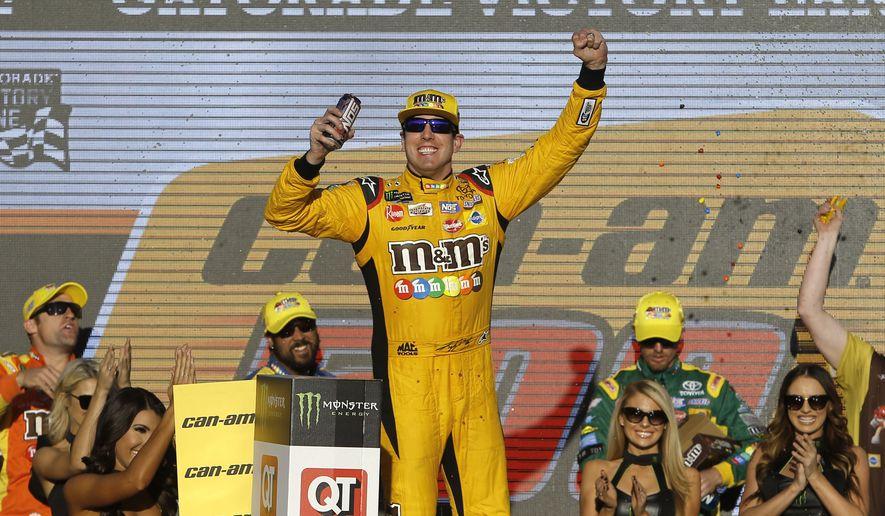 Kyle Busch (18) celebrates after winning a NASCAR Cup Series auto race on Sunday, Nov. 11, 2018, in Avondale, Ariz. (AP Photo/Rick Scuteri)