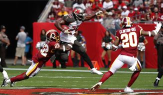 Tampa Bay Buccaneers running back Peyton Barber (25) is stopped by Washington Redskins defensive back Deshazor Everett (22) as free safety Ha Ha Clinton-Dix (20) close in during the first half of an NFL football game Sunday, Nov. 11, 2018, in Tampa, Fla. (AP Photo/Mark LoMoglio)