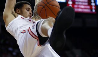 Ohio State guard Duane Washington, top, dunks between teammate guard C.J. Jackson, left, and Purdue Fort Wayne guard Jarred Godfrey during the first half of an NCAA college basketball game in Columbus, Ohio, Sunday, Nov. 11, 2018. (AP Photo/Paul Vernon)