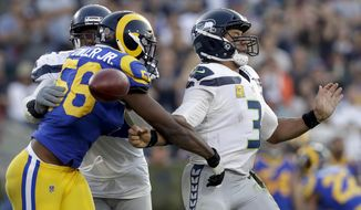 Los Angeles Rams defensive end Dante Fowler forces a fumble by Seattle Seahawks quarterback Russell Wilson during the second half in an NFL football game Sunday, Nov. 11, 2018, in Los Angeles.(AP Photo/Alex Gallardo)