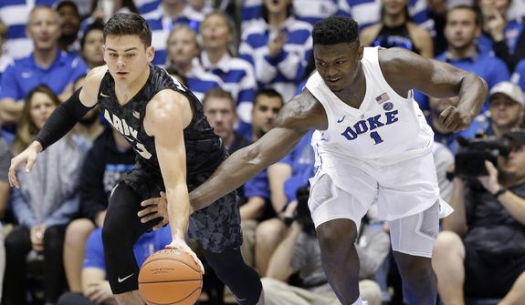 Army's Tommy Funk, left, and Duke's Zion Williamson (1) chase the ball during the first half of an NCAA college basketball game in Durham, N.C., Sunday, Nov. 11, 2018. (AP Photo/Gerry Broome)