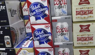 In this photo taken on Thursday, Nov. 8, 2018, cases of Pabst Blue Ribbon and Coors Light are stacked next to each other in a Milwaukee liquor store. Pabst Brewing Company and MillerCoors are heading to trial starting Monday, Nov. 12, to settle a contract dispute in which Pabst accuses the brewing giant of trying to undermine its competitor by breaking a contract to make their products. (AP Photo/Ivan Moreno)