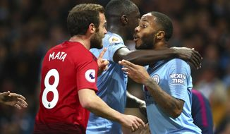 Manchester City's Benjamin Mendy, centre, holding Manchester City's Rahhem Sterling as he argues with Manchester United's Juan Mata during the English Premier League soccer match between Manchester City and Manchester United at the Etihad stadium in Manchester, England, Sunday, Nov. 11, 2018. (AP Photo/Dave Thompson)