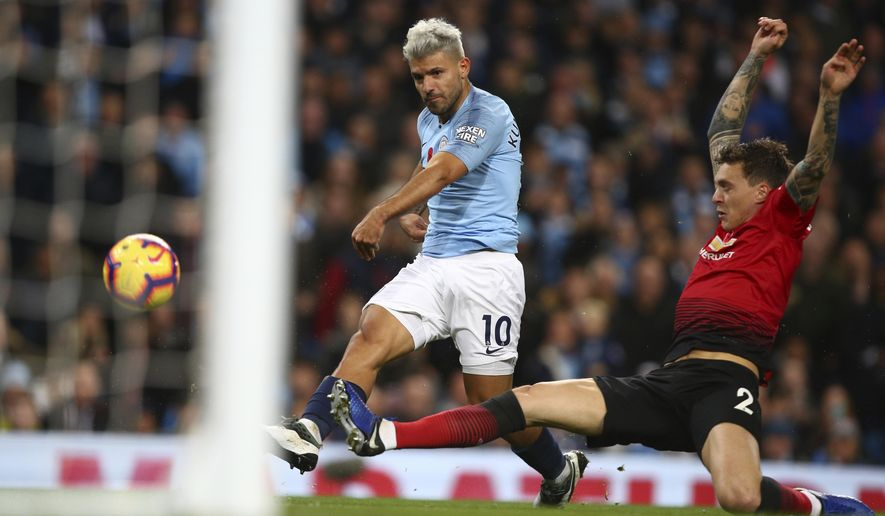 Manchester City's Sergio Aguero shoots past Manchester United's Victor Lindelof to score his team's second goal during the English Premier League soccer match between Manchester City and Manchester United at the Etihad stadium in Manchester, England, Sunday, Nov. 11, 2018. (AP Photo/Dave Thompson)