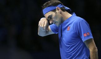 Switzerland's Roger Federer wipes his face during his ATP World Tour Finals singles final tennis match against Japan's Kei Nishikori at the O2 Arena in London, Sunday Nov. 11, 2018. (AP Photo/Tim Ireland)