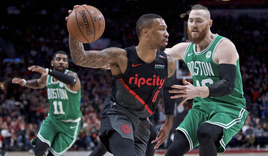 Portland Trail Blazers guard Damian Lillard, left, dribbles past Boston Celtics center Aron Baynes during the first half of an NBA basketball game in Portland, Ore., Sunday, Nov. 11, 2018. (AP Photo/Craig Mitchelldyer)