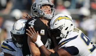 Oakland Raiders quarterback Derek Carr (4) is hit between Los Angeles Chargers linebacker Uchenna Nwosu, left, and defensive tackle Corey Liuget during the first half of an NFL football game in Oakland, Calif., Sunday, Nov. 11, 2018. (AP Photo/John Hefti)