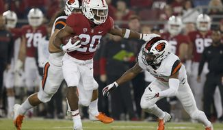 CORRECTS DATE - Stanford running back Bryce Love (20) stiff arms Oregon State cornerback Shawn Wilson (2) as he rushes for a touchdown in the first half during an NCAA college football game on Saturday, Nov. 10, 2018, in Stanford, Calif. (AP Photo/Tony Avelar)